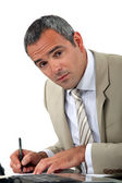 Attentive businessman making notes — Stock Photo