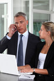 Boss working closely with female colleague — Stock Photo