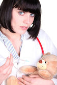 Woman making injection to teddy bear — Стоковое фото
