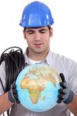Artisan looking at globe — Stock Photo