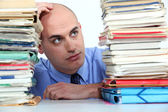 Office worker looking at stacks of files — Stock Photo