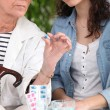 Foto Stock: Old woman and daughter sat with prescription drugs