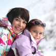 Mother and daughter on snowy mountain — Stock Photo