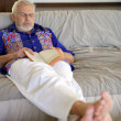 Senior holding a book and sleeping on the couch — Stock Photo #9970528