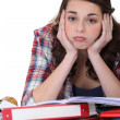 Stock Photo: Bored student with pile of homework