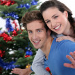 Portrait of cheerful young couple posing near Christmas tree — Stock Photo