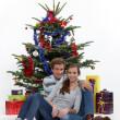 pareja sentada en el piso delante de árbol de Navidad — Foto de Stock