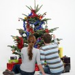 Couple sat by Christmas tree — Stock Photo