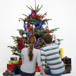 Stock Photo: Couple sat by Christmas tree