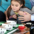 Girl looking at scale model of future home — Stock Photo