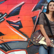 Woman with guitar in front of graffiti — Stock Photo