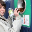 Woman putting glass in a recycling bin — Stock Photo