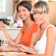 Two girls eating in the kitchen — Stock Photo