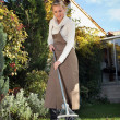 Woman raking leaves in  the garden - Stock Photo