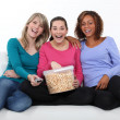 Friends laughing and eating popcorn — Stock Photo