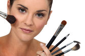 Woman posing with her make-up brushes — Stockfoto
