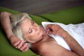 Sênior mulher dormindo em uma toalha — Foto Stock