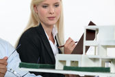Architect and co-worker looking at model building — Stock Photo