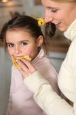 Mother giving her daughter a snack — Stock Photo
