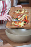 Women removing vegetables peeling from chopping board — Stock Photo