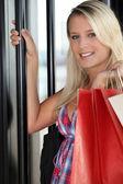Jonge blonde opening deur — Stockfoto