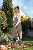 Woman raking leaves in the garden — Stock Photo