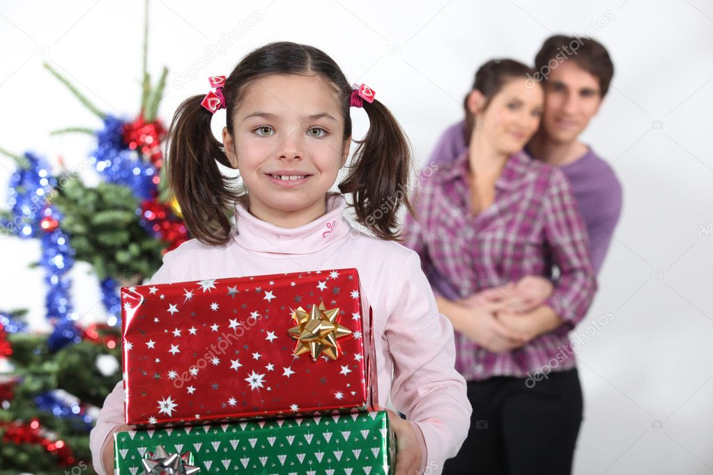 Girl and parents with Christmas presents — Stock Photo #9971675