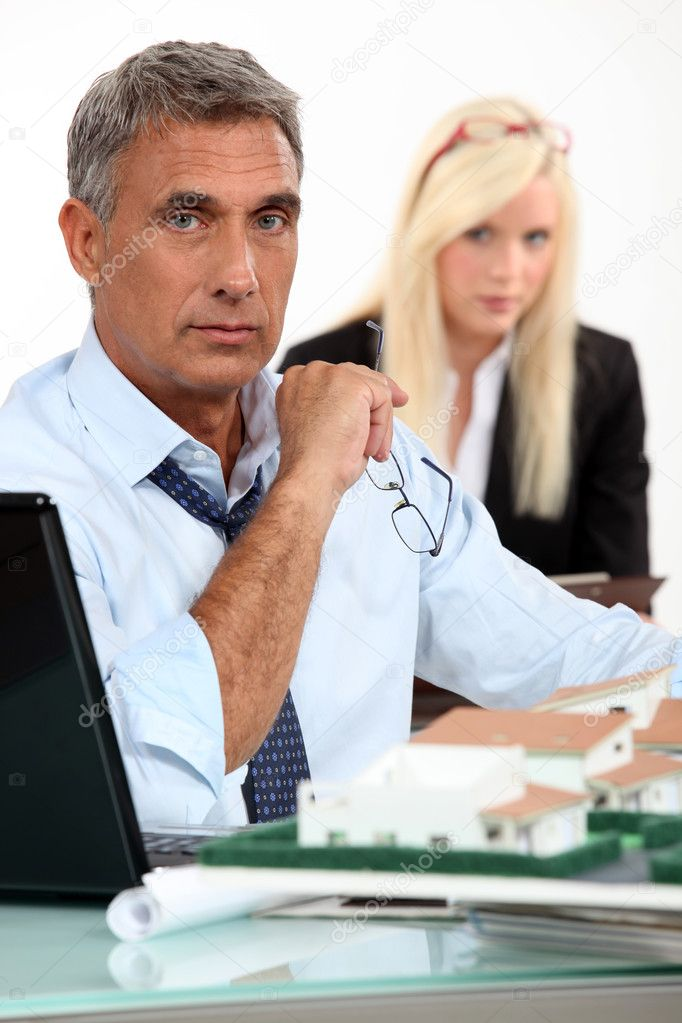 Male architect with laptop and model of housing development — Stock Photo #9971936