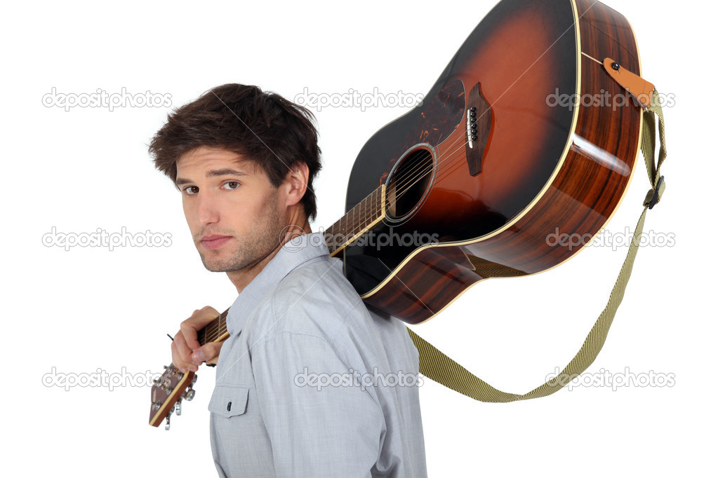 Young man carrying a guitar on his shoulder  Stock Photo #9972174