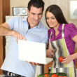 Couple cooking with a laptop - Stockfoto