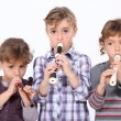 Three young girls playing the recorder - Stockfoto
