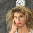 Young woman with a clock on her head — Stockfoto