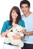 Young couple with a teddy bear — Stock Photo