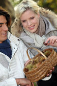 Couple with basket of chestnuts — Stock Photo