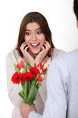 Surprised woman receiving flowers from her boyfriend — Stock Photo