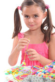 Little girl making necklace — Stock Photo