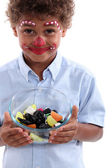 Little boy made-up as a clown with bowl of candy — Stock Photo