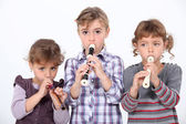 Three young girls playing the recorder — Stock Photo