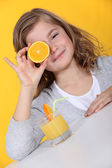 Girl covering her eye with orange slice — Stock Photo