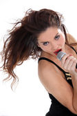 Attractive brunette singing into microphone — Stock Photo