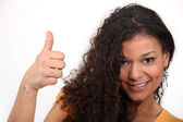 Woman with curly hair giving the thumb — Stock Photo