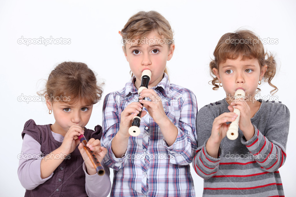 Three young girls playing the recorder — Stock Photo #9995672