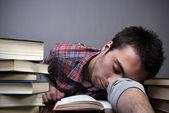 Young man sleeping on books — Stock Photo