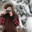 Woman photographer in winter forest — Stok fotoğraf