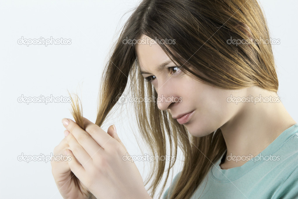 Woman with worried look on her face looking at the tips of her dry, damaged hair. — Stock Photo #9523926