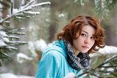 Retrato de una joven en un fondo de un bosque de invierno — Foto de Stock