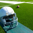 American Football Helmet on the Bench - Stock Photo