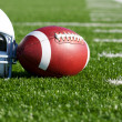 Football and Helmet on the Field - Stock Photo