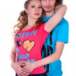 Stock Photo: Young man and woman embracing dressed in colorful T-shirts