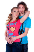 Young man and woman embracing dressed in colorful T-shirts — Stock Photo